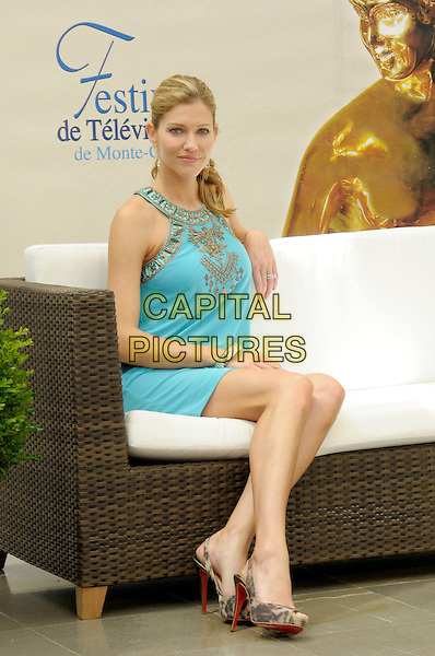 "TRICIA HELFER.Photocall for ""Battlestar Galactica"" during the 49th Monte Carlo Television Festival at the Grimaldi Forum, Monte-Carlo, Monaco..June 10th, 2009.full length sitting couch sofa blue gold turquoise dress beige detail pattern .CAP/RD.©Richard Dean/Capital Pictures."