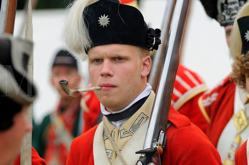 Redcoat soldier of His Majesty's 62nd Regiment of Foot, with characteristic starred pewter cap badge, smokes a clay pipe while awaiting orders at a Revolutionary War re-enactment at Fort Ticonderoga, New York, USA.