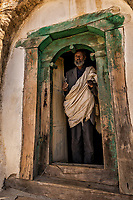 The priest holds his cross in the door way of the Mikael Melehayzenghi rock hewn church