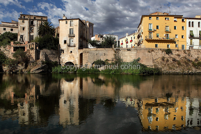 Houses in Mora d'Ebre reflected in the Ebro river, Ribera d'Ebre, Tarragona, Spain. An old pier can be seen next to the three-floors building on the left with a hole to park the boat. Picture by Manuel Cohen