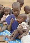 A child feeds their sibling as part of a supplemental feeding program for malnourished children and mothers run by the clinic of the Loreto School in Rumbek, South Sudan. The school is run by the Institute for the Blessed Virgin Mary--the Loreto Sisters--of Ireland.