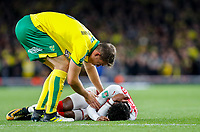 Christoph Zimmermann of Norwich City checks on injured Ainsley Maitland-Niles of Arsenal during the Carabao Cup match between Arsenal and Norwich City at the Emirates Stadium, London, England on 24 October 2017. Photo by Carlton Myrie.