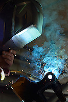 Welder in mask working on steel at factory, France