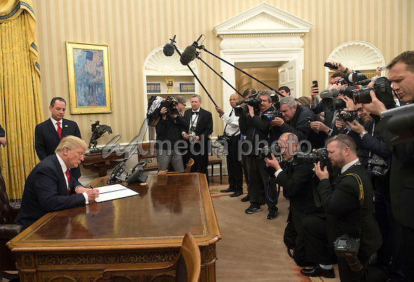 President Donald Trump signs his first executive order as president, ordering federal agencies to ease the burden of President Barack Obama's Affordable Care Act, in the Oval Office at the White House in Washington, D.C. on January 20, 2017. Photo Credit: Kevin Dietsch/CNP/AdMedia