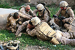 Lance Cpl. Matthew W. McElhinney has been shot in the back just below his body armor and just above his right buttock during a gun battle with Taliban fighters near Marjah, Afghanistan. There is no exit wound, and the extent of his injury is unknown. But McElhinney is bleeding profusely and in a lot of pain as his buddies from Company L, 3rd Battalion, 6th Marine Regiment work to stop the loss of blood and to keep him from going into shock. March 10, 2010. DREW BROWN/STARS AND STRIPES