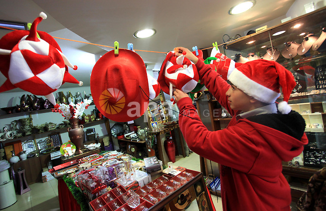 A Palestinian vendor decorates his shop during the preparations ahead of Christmas, in the West Bank City of Ramallah, 23 December 2013. Photo by Issam Rimawi