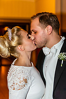 Norwegian bride and groom kissing as they enter their wedding reception, Trysil, Norway.