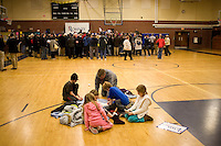 A group plays Bananagrams while Mitt Romney speaks to the crowd in the overflow area in a gymnasium at a Romney town hall campaign event at McKelvie Intermediate School in Bedford, New Hampshire, on Jan. 9, 2012.  Romney is seeking the 2012 Republican presidential nomination.