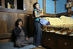 Watching television. A poor farming family living in a traditional dwelling finding it hard to make ends meet. Punakha, Bhutan..Bhutan the country that prides itself on the development of 'Gross National Happiness' rather than GNP. This attitude pervades education, government, proclamations by royalty and politicians alike, and in the daily life of Bhutanese people. Strong adherence and respect for a royal family and Buddhism, mean the people generally follow what they are told and taught. There are of course contradictions between the modern and tradional world more often seen in urban rather than rural contexts. Phallic images of huge penises adorn the traditional homes, surrounded by animal spirits; Gross National Penis. Slow development, and fending off the modern world, television only introduced ten years ago, the lack of intrusive tourism, as tourists need to pay a daily minimum entry of $250, ecotourism for the rich, leaves a relatively unworldly populace, but with very high literacy, good health service and payments to peasants to not kill wild animals, or misuse forest, enables sustainable development and protects the country's natural heritage. Whilst various hydro-electric schemes, cash crops including apples, pull in import revenue, and Bhutan is helped with aid from the international community. Its population is only a meagre 700,000. Indian and Nepalese workers carry out the menial road and construction work.