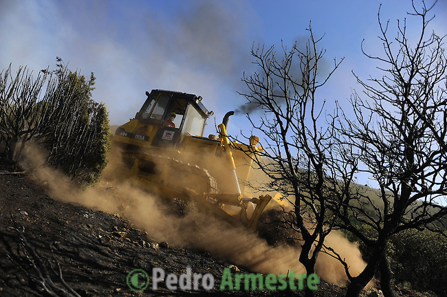 A man drives a bulldozer around the area where a wildfire burns in Canizar del Olivar, near Teruel, on July 24, 2009. Deadly summer wild fires spread across Spain, France, Italy and Greece on Friday with holidaymakers rescued from beaches and thousands of firefighters brought into the battle. on July 24, 2009. (C) Pedro ARMESTRE