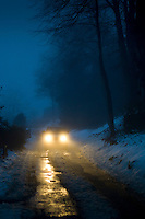 Car headlamps pierce the gloom on foggy day in The Cotswolds, UK