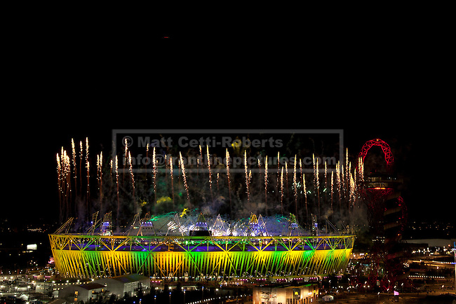 12/08/2012. LONDON, UK. Fireworks erupt over the Olympic Park as Olympic Stadium is lit in the Brazilian national colours, the host nation for the next summer Olympics in 2016, during the closing ceremony of the 2012 Summer Olympics in London today (12/08/12). The Games of the 30th Olympiad today come to a close in London after two weeks of athletics and sports competition carried out by 204 countries from around the world. Photo credit: Matt Cetti-Roberts