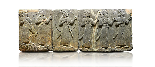 Hittite relief sculpted orthostat stone panel of Royal Buttress Basalt, Karkamıs, (Kargamıs), Carchemish (Karkemish), 900-700 B.C. Warriors. Anatolian Civilisations Museum, Ankara, Turkey.<br /> <br /> Right panel - Three figures each with a long dress, a thick belt and curly hair. The figure in front holds a spear with a broken tip in his left hand and a leafy branch in his right hand. The figure in the middle made his left hand a fist, and he carries a tool with his right hand at the level of his head. They are followed with a figure holding a sceptre in his left hand. All three have each a long sword at their waist. <br /> <br /> Against a white background.