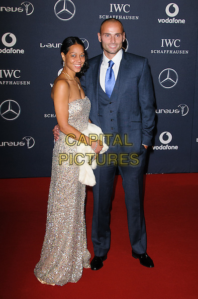 guest & Andy Turner.Arrivals at the Laureus 2012 World Sports Awards held at the Queen Elizabeth II Centre, London, England..February 6th, 2012.full length grey gray suit gold strapless dress side.CAP/CJ.©Chris Joseph/Capital Pictures.