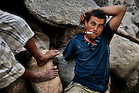 """A young Honduran immigrant, having his arm amputated by a train during his previous attempt to get illegally to the United States, smokes marijuana on the bank of Suchiate river on the Guatemala-Mexico border, on 23 May 2011. Between 2010 and 2015, the US and Mexico have apprehended almost 1 million illegal immigrants from El Salvador, Honduras, and Guatemala. While the economic reasons remain the most frequent motivation for people from Central America to illegally immigrate to the US, thousands of Salvadorans, Guatemalans, and Hondurans, many of them minors, seek asylum in the US due to the thriving crime and gang-related violence in their region (known as the Northern Triangle). Taking an exhausting and risky journey, riding thousands of miles atop the cargo trains, facing a physical danger and extortion from the organized crime groups that control migrant routes, the """"undocumented"""" still flee to the US, looking for their American dream."""