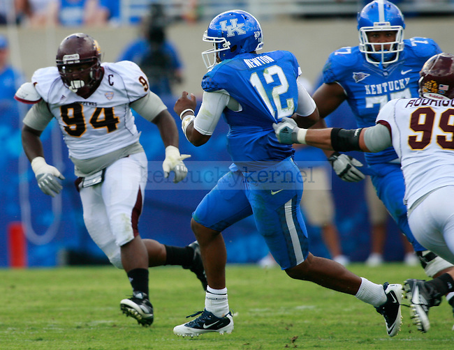 UK quarterback Morgan Newton scrambles past Central Michigan defensive end Caesar Rodriguez and other defenders during the second half of UK's first home game against Central Michigan, Saturday, Sept. 10, 2011 in Lexington, Ky.  Photo by Brandon Goodwin | Staff