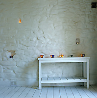 Lit candles in colourful glass holders line a wooden table against a whitewashed stone wall