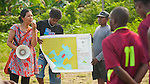 Conservation Fellow Wida Sulistyaningrum quizzes community members on no take zones before a soccer match hosted by RARE.