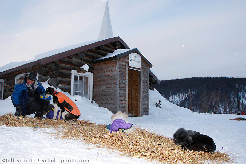 Friday March 12 , 2010   Sonny Lindner feeds his dogs as they rest on straw in front of the Ruby Bible Church at the village checkpoint  of Ruby