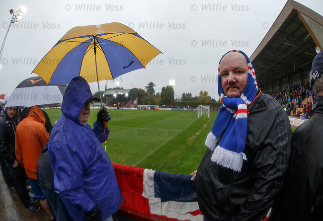 Rangers fans getting soaked next to the hedge at Glebe Park