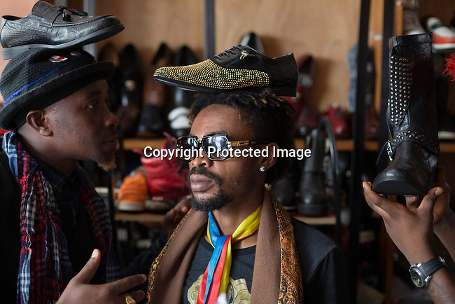 """KINSHASA, DEMOCRATIC REPUBLIC OF CONGO - FEBRUARY 12: Mzee Kindingu (c), the leader of the Sapeurs group The Leopards shops for shoes in one of the fashion shops in Matonge area February 12, 2016 in Kinshasa, DRC. The word Sapeur comes from SAPE, a French acronym for Société des Ambianceurs et Persons Élégants. or Society of Revellers and Elegant People. and it also means, .to dress with elegance and style"""". Most of the young Sapeurs are unemployed, poor and live in harsh conditions in Kinshasa, a city of about 10 million people. For many of them being a Sapeur means they can escape their daily struggles and dress like fashionable Europeans. Many hustle to build up their expensive collections. Most Sapeurs could never afford to visit Paris, and usually relatives send or bring clothes back to Kinshasa. (Photo by Per-Anders Pettersson)"""