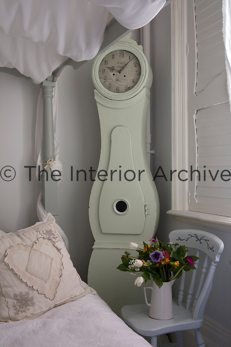 A pale green Mora clock stands in a corner of the guest bedroom