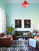The study's sofa is by Arne Norell, the 1930s armchairs are French, the cocktail table is a Paris flea-market find, the pillows are from a Marrakech souk and the floor lamps are by Jielde; the tiles are Popham Design's Fretwork-on-Four. The ceiling light fixture is vintage and the wall are painted in a custom blue colour.