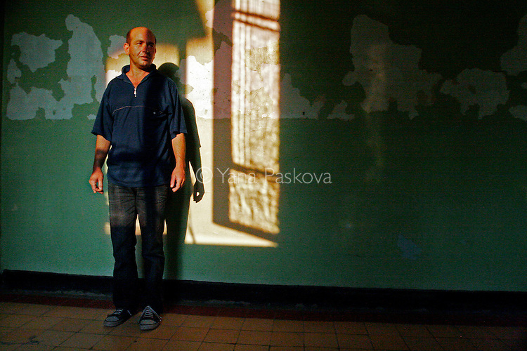 Y. E. hangs motionless by the peeling walls against the sunset-outlined window shadow. He has been in and out of the hospital since 1998, and has received a diagnosis for multiple-personality disorder and schizophrenia.