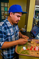 Rolling joints that will be distributed for free at a 4/20 event in Denver. Medicine Man Denver is the single largest legal medical and recreational marijuana dispensary in Denver, Colorado USA. Their 20,000 sq. ft. facility will soon double in size. Radio frequency ID tags and 65 video cameras allow the State of Colorado to track inventory through the growing process and all plant weight is accounted for. Medicine Man won the High Times' Cannabis Cup for best sativa (Jack Herer). 20-30 strains are available for sale daily.
