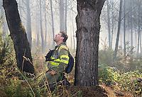 Fecha: 23-07-2015.-  Lugo.- Incendios de Verano.-   Debido a las continuas olas de calor y a la falta de precipitaciones, esta todo tan seco que arde con mucha facilidad, medios aéreos y terrestres combaten el fuego. Hoy en Lugo fueron varios los incendios que durante todo el día quemaron pinos, y pastos. En la imagen un incendio cerca del pueblo Castelo Grande, en Lugo. El fuego comenzó sobre las 10:30 de la mañana. En la foto un brigadistas respira dificultosamente después de un momento angustioso provocado por el intenso humo.