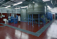 The interior of a chemical processing lab with a technician at work.