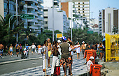 Rio de Janeiro, Brazil. Beach vendors; berimbau players and prawn kebab sellers on the road next to Ipanema Beach.