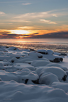 Snow-obscured beach rocks catch the last rays of the sun as it sets over Alaska's Cook Inlet.