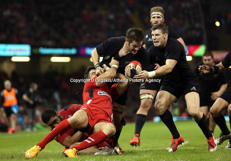 Pictured: Richie McCaw of New Zealand (C) is brought down by Mike Phillips of Wales (L) Saturday 22 November 2014<br />