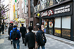 Pedestrians walk past the Japan's first Carl's Jr. burger restaurant located in Tokyo's Akihabara district, on March 2, 2016, Japan. The Californian fast food restaurant follows on the heels of Shake Shack in entering the Japanese market. Mitsuuroko Group Holdings Co., Ltd. has signed a franchise agreement to operate Carl's Jr. branches in Japan with the first to open to the public on March 4th. (Photo by Rodrigo Reyes Marin/AFLO)