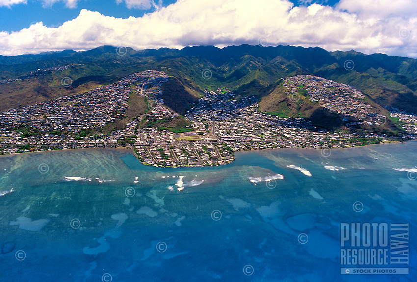 Aerial view of east Oahu coastline with homes on hillsides and in the valleys and a  blue sweeping ocean
