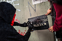 A radical student of the Universidad Nacional de Colombia spray paints a political slogan on the wall during a protest march against government's policies and corruption within the public educational system in Bogotá, Colombia, 24 October 2019.