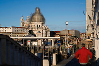 Worker pushing wheel barrow, with the background of Scaffolding on the dome of San Maria della Salute, Grand Canal Venice, Italy