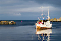 Wooden fishing boat returns to harbor, Stamsund, Lofoten islands, Norway