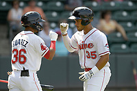 Third baseman Brandon Howlett (35) of the Greenville Drive is greeted by Kervin Suarez (36) after hitting his first home run of the season in a game against the Hickory Crawdads on Tuesday, April 30, 2019, at Fluor Field at the West End in Greenville, South Carolina. Hickory won, 5-4. (Tom Priddy/Four Seam Images)