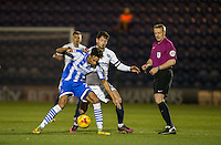 Kurtis Guthrie of Colchester United & Joe Jacobson of Wycombe Wanderers are watched by Referee Trevor Kettle during the Sky Bet League 2 match between Colchester United and Wycombe Wanderers at the Weston Homes Community Stadium, Colchester, England on 21 February 2017. Photo by Andy Rowland / PRiME Media Images.