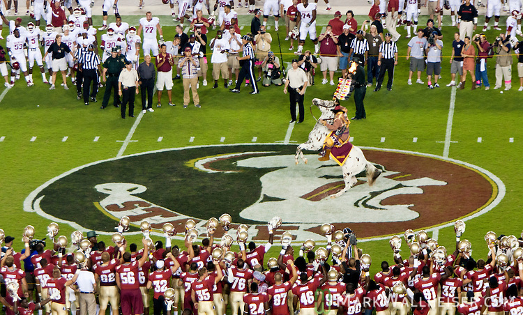 Florida State and Oklahoma football teams watch as the FSU mascot, Osceola atop his horse Renegade plant a flaming spear at mid-field prior to the start of their NCAA football game in Tallahassee, Florida Sept 17, 2011.  The number one ranked Oklahoma Sooners defeated the 5th ranked Florida State Sminoles 23-13.