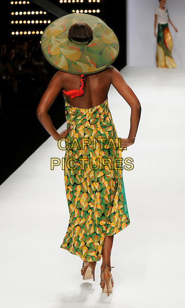 NAOMI CAMPBELL .At the Issa Show, London Fashion Week Day 3, Somerset House, London, England, UK,.September 20th 2009..full length modeling catwalk runway green and yellow print sarong cover up beach wear swimwear hat matching hands on hips halterneck brown sandals heels back rear behind .CAP/CAN.©Can Nguyen/Capital Pictures.