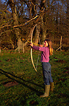 ARM4F8 Young girl with bow firing arrow in a field