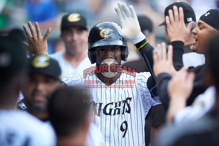 Luis Robert (9) of the Charlotte Knights high fives teammate after scoring a run against the Durham Bulls at BB&T BallPark on July 31, 2019 in Charlotte, North Carolina. The Knights defeated the Bulls 9-6. (Brian Westerholt/Four Seam Images)