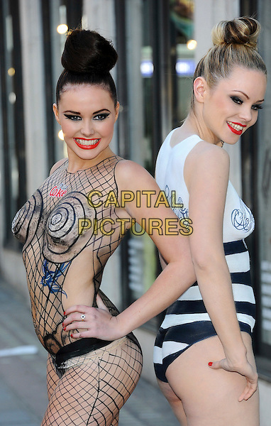 JPG Models.JPG & Diet Coke - photocall at Harvey Nichols, Knightsbridge, London, England..Two models pose for photos as award-winning body artist Carolyn Roper paints them as Diet Coke bottles, recreating Jean Paul Gaultier's latest 'Night & Day' designs for the brand..April 16th, 2012.half length posing black naked nude skin hand on hip hair up side white red lipstick striped stripes lipstick red fishnet hand    .CAP/CJ.©Chris Joseph/Capital Pictures.