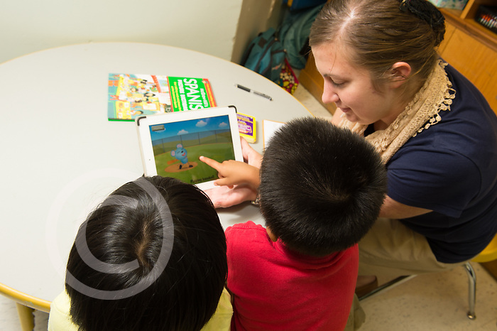 Education preschool 3-4 year olds, speech therapist at work with two boys using iPad tablet computer