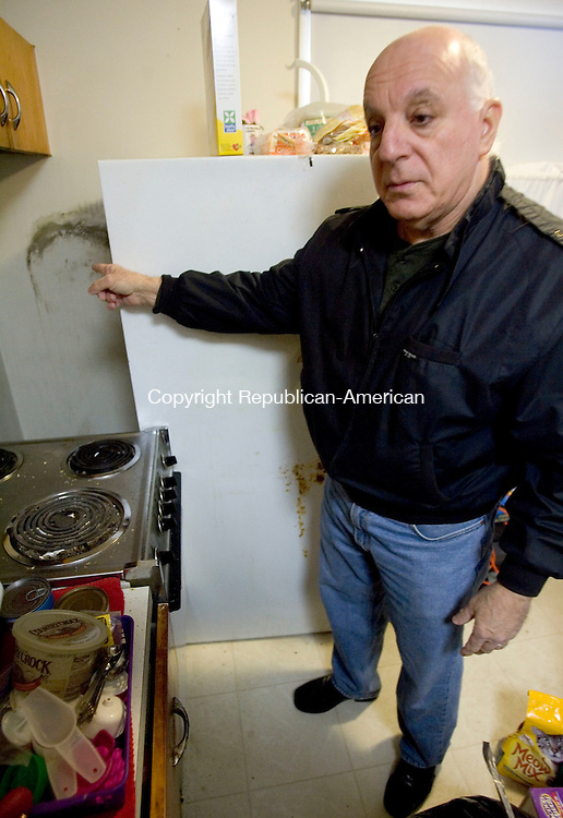 NAUGATUCK, CT. 24 January 2012-012412SV08-Emidio Cerasale of Naugatuck moves a refrigerator from a neighbor's apartment to show the mold growing on the wall behind it at the Oak Terrace apartment complex in Naugatuck Tuesday. People are complaining of mold at the Oak Terrace complex, which is run by the Naugatuck Housing Authority. .Steven Valenti Republican-American