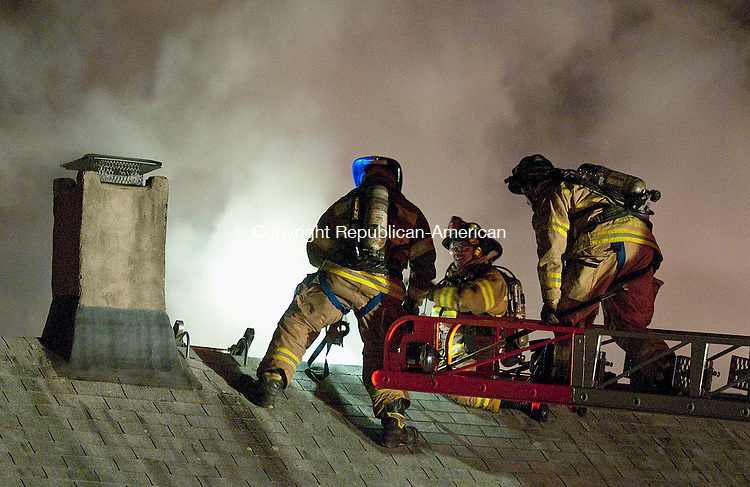 WATERBURY, CT, 23 NOVEMBER 2011-112311JS13-Waterbury firefighters work on the roof as they battle a fire at a two-family home 25 Seymour Street in Waterbury on Wednesday night. Two tenants were taken to area hospitals.  The second floor and attic were heavily damaged by fire. The cause of the fire is under investigation. <br />  Jim Shannon Republican-American