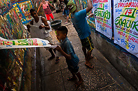 """Colombian sign painters take down just-finished music party posters in the sign painting workshop in Cartagena, Colombia, 12 December 2017. Hidden in the dark, narrow alleys of Bazurto market, a group of dozen young men gathered around José Corredor (""""Runner""""), the master painter, produce every day hundreds of hand-painted posters. Although the vast majority of the production is designed for a cheap visual promotion of popular Champeta music parties, held every weekend around the city, Runner and his apprentices also create other graphic design artworks, based on brush lettering technique. Using simple brushes and bright paints, the artisanal workshop keeps the traditional sign painting art alive."""
